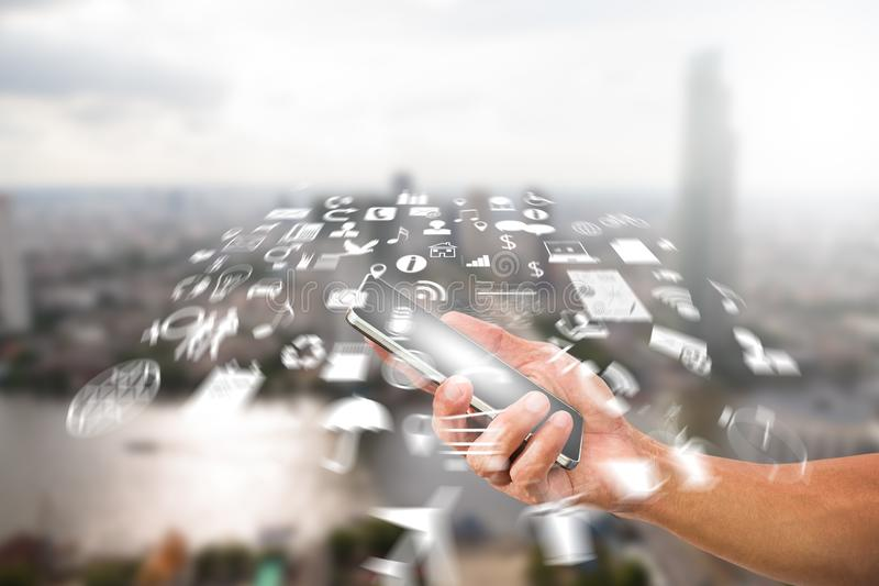 Man`s hand holding smartphone with radial blurred business icon on blurred city background. Man& x27;s hand holding smartphone with radial blurred business icon royalty free stock photo