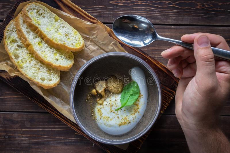 Man`s hand holding spoon over a cappuccino soup with mushrooms on wooden cutting board. Three slices of white bread on the brown stock images