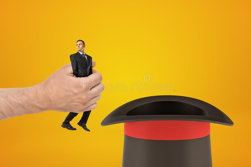 Man`s hand holding tiny businessman and putting him in black top-hat on amber background with some copy space above the. Hat. Business secrets. Top-hat plan stock photo
