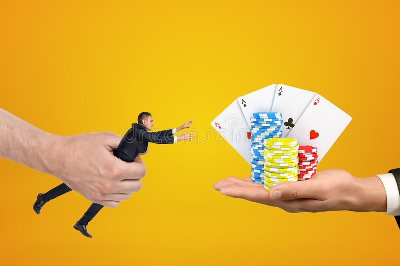 Man`s hand holding tiny businessman who is reaching out with both hands for cards and chips on another man`s palm on. Amber background. Gambling addiction stock images