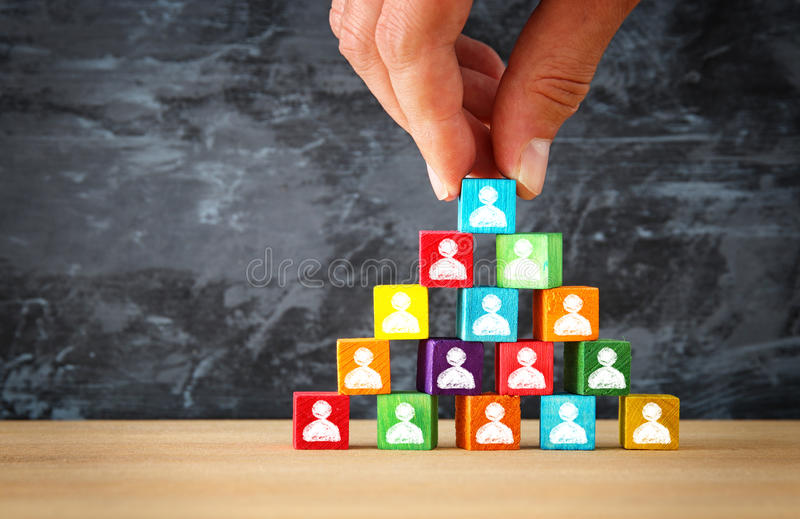 Man& x27;s hand holding a top of wooden blocks pyramid with people icons over wooden table. Human resources and management concept royalty free stock images