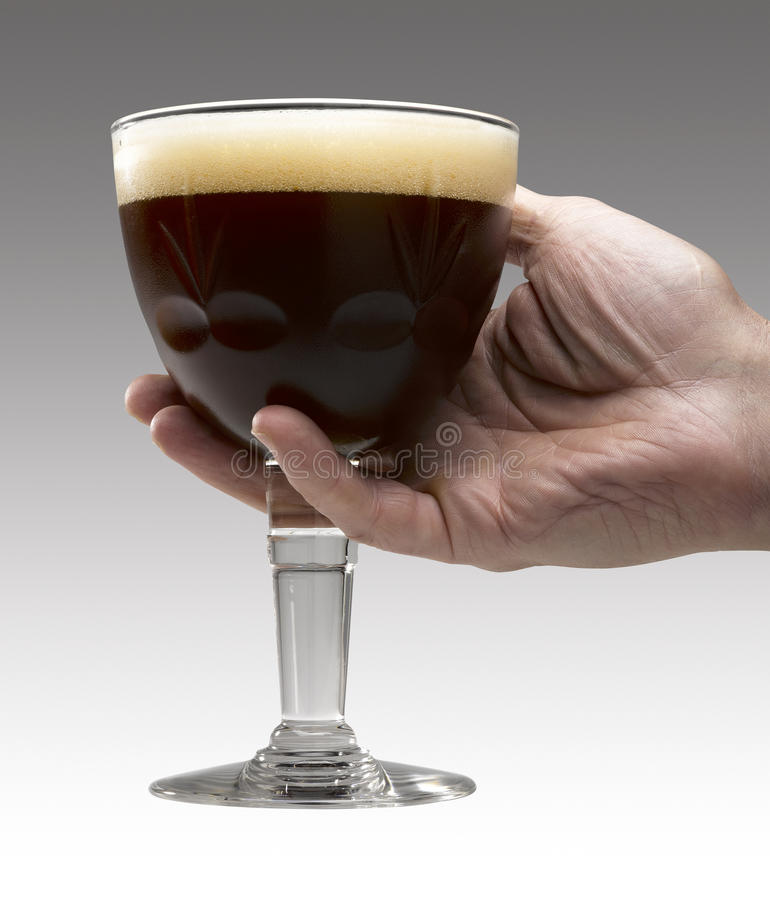 Man's hand holding a Trappist beer stock image