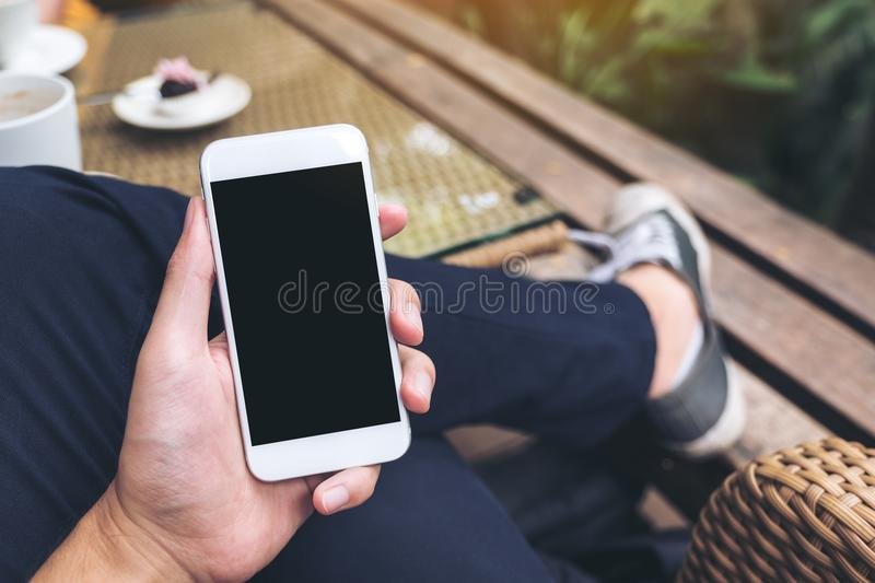 A man`s hand holding white mobile phone with blank black screen in cafe royalty free stock photo