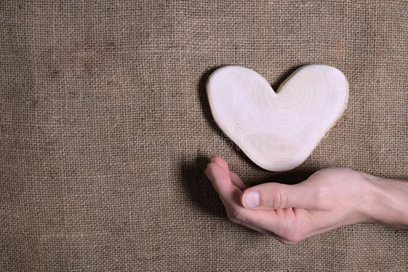 Man`s hand holding wooden heart on natural canvas burlap background. Sustainable eco-friendly Valentine`s day. Earth tone brown stock image