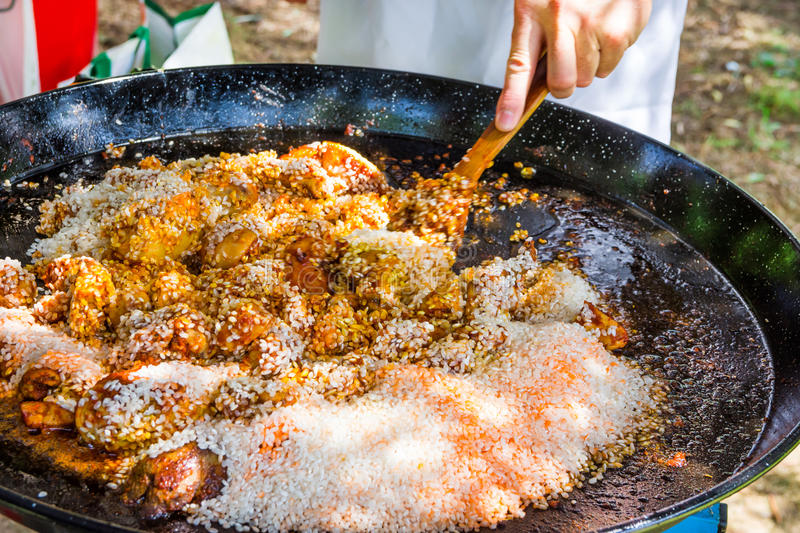Man`s hand holding wooden turner, mixing uncooked rice with fried chicken meat tomato sauce spices. Preparing paella or jambalaya royalty free stock images