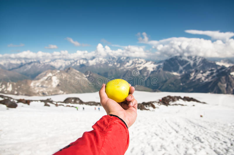 A man`s hand holds an apple against the background of snow-capped mountains and snow underfoot. stock photo