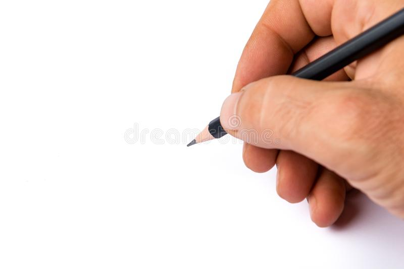 Man`s hand holds a black pencil against white background, select royalty free stock images