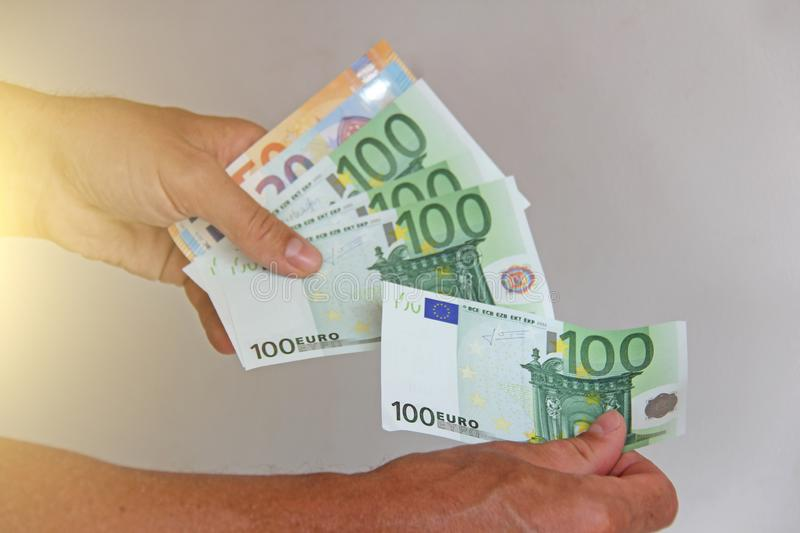 The man`s hand holds the 100 euro, considers them and pays. Paper money euros in the hands.  stock photos