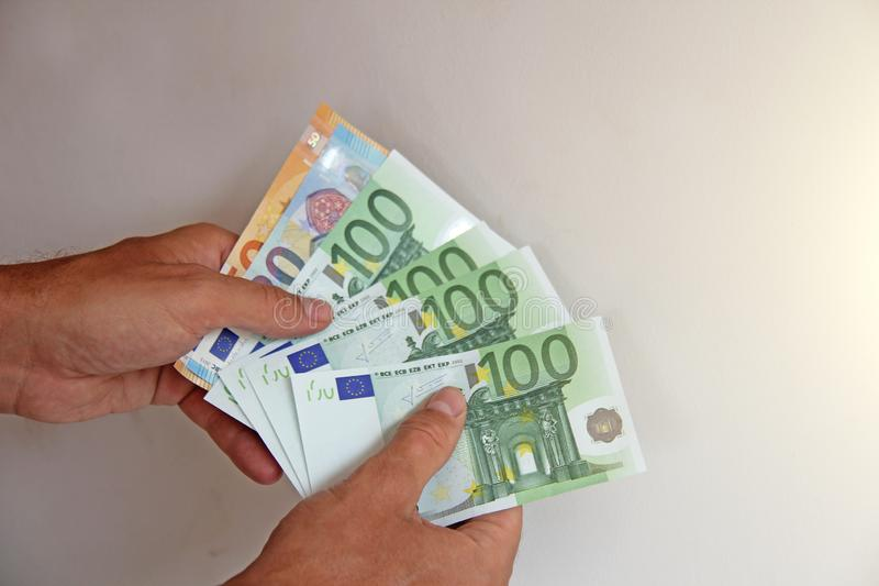 The man`s hand holds the 100 euro, considers them and pays. Paper money euros in the hands.  royalty free stock photos