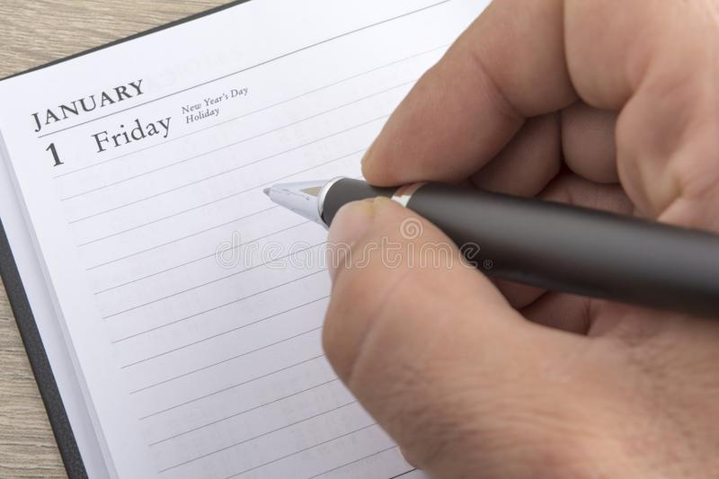 Man`s hand holds a metal pen ready to set goals for the new year. Close up royalty free stock photography