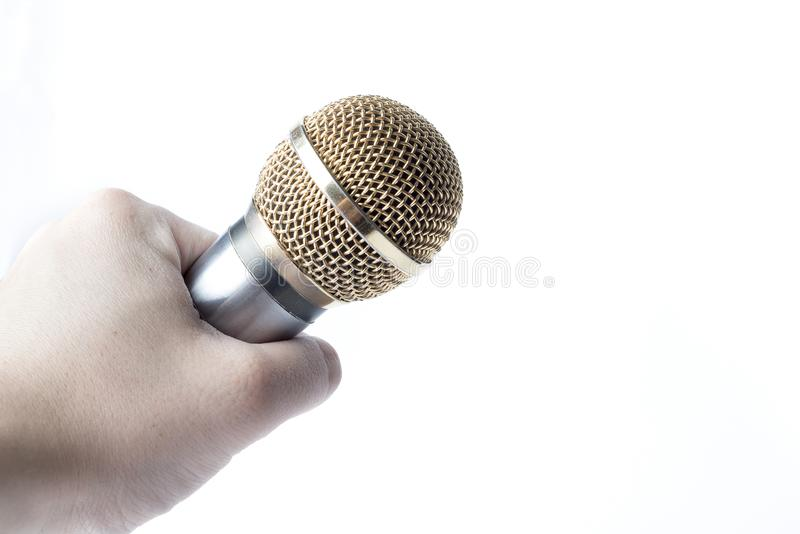 A man`s hand holds a microphone on a white background. stock image