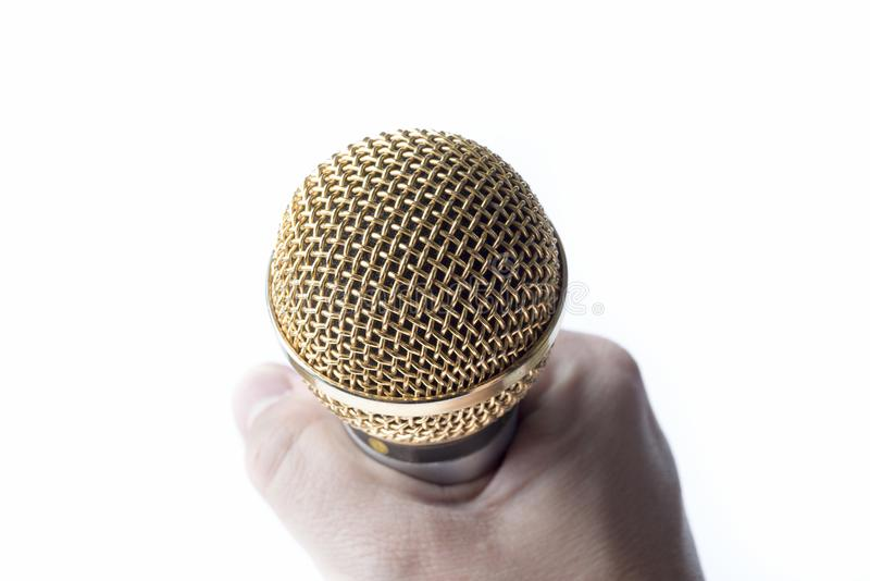 A man`s hand holds a microphone on a white background. royalty free stock image