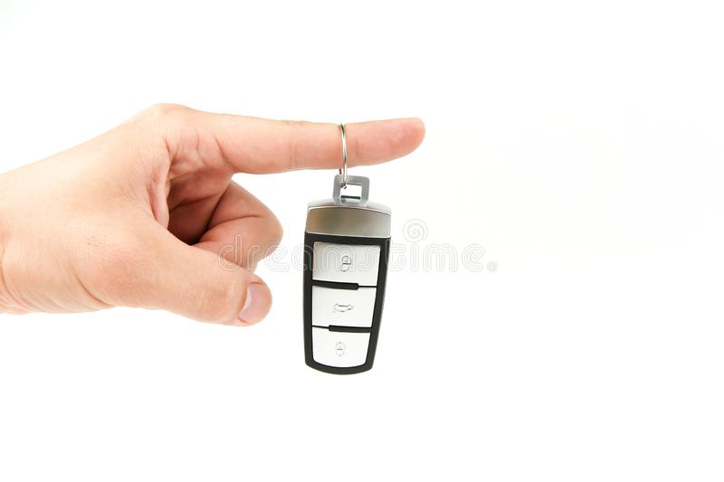 Man`s hand holds new car key on white background with copy space. Car key chain in the palm of a hand royalty free stock images