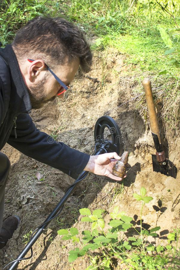 Man`s hand holds part of the detonator to the bomb from World War II. A metal detector in the other hand. The shovel lies o. The man`s hand holds part of the royalty free stock photography