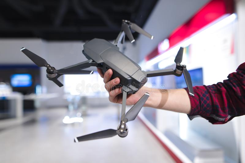 Man`s hand holds a quadcopter in the background of a electronics store. Purchase a dron in a hardware store. A man`s hand holds a quadcopter in the background of royalty free stock photo