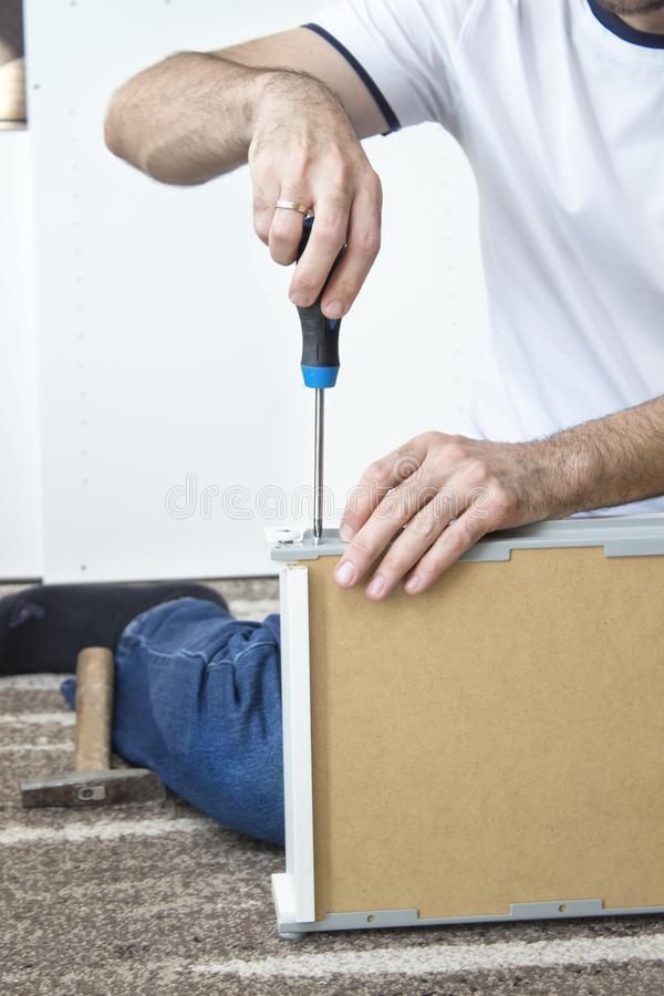 Man`s hand holds the screwdriver and screws the screw that secures the drawer guide. The man`s hand holds the screwdriver and screws the screw that secures the royalty free stock image