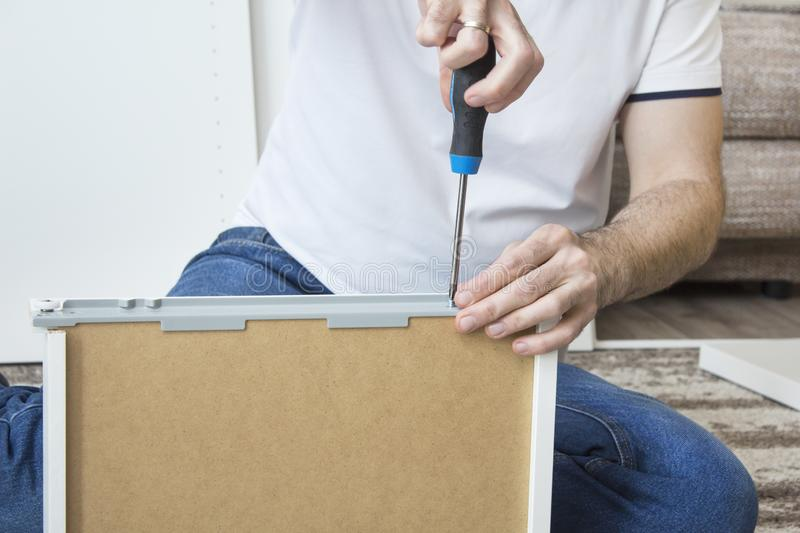 The man`s hand holds the screwdriver and screws the screw that secures the drawer guide. The man`s hand holds the screwdriver and screws the screw that secures royalty free stock images