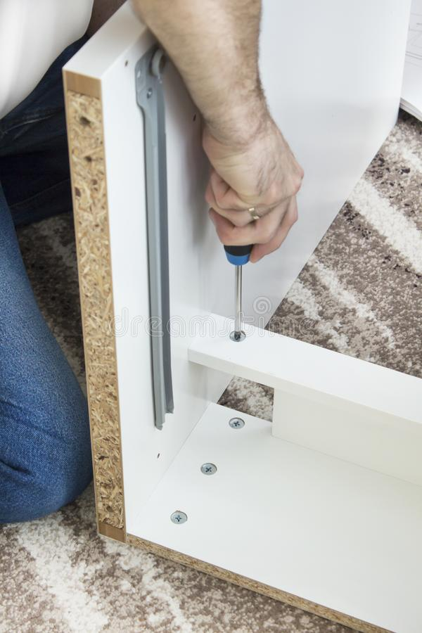 The man`s hand holds the screwdriver and screws the screw that secures the drawer guide. The man`s hand holds the screwdriver and screws the screw that secures royalty free stock photos