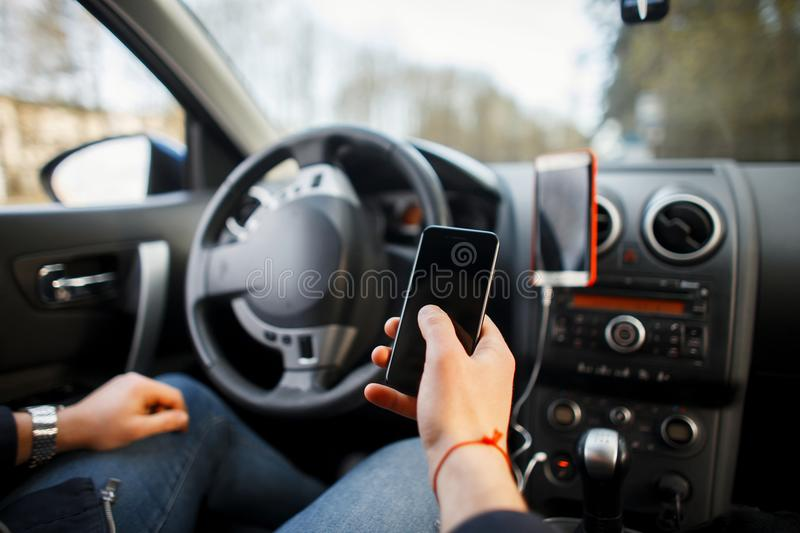 Man`s hand holds a smartphone in the car. A man`s hand holds a modern smartphone in the car`s interior royalty free stock photo