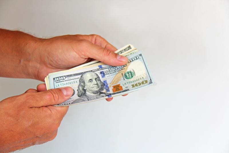 The man`s hand holds US dollars, counts them and pays. Paper money dollars in hand stock photography