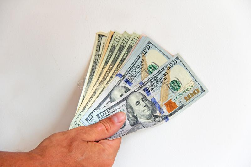 The man`s hand holds US dollars, counts them and pays. Paper money dollars in hand.  stock image