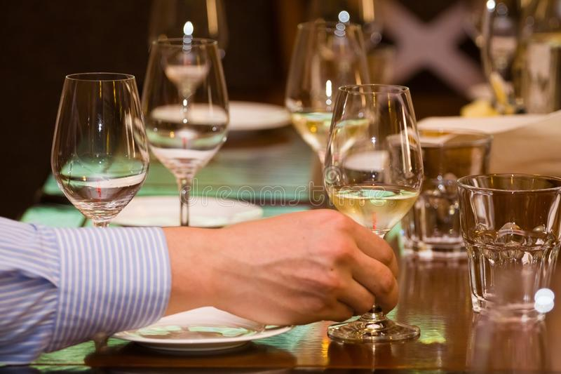 Man`s hand holds a wineglass with white wine during wine testing in a restaurant. Man`s hand holds a wineglass with rare and expensive white wine during wine stock image