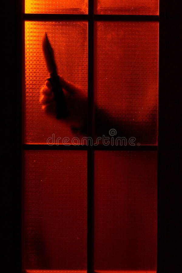 Man`s hand with a knife behind the door with red backlight stock photography