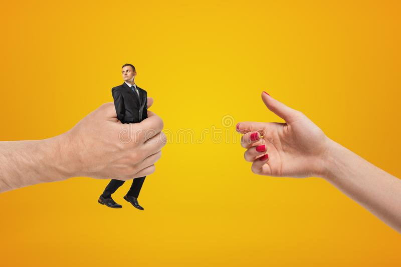 Man`s hand on the left holding tiny businessman and giving him to woman whose hand is on the right on amber background. Human resources. Corporate management stock photo