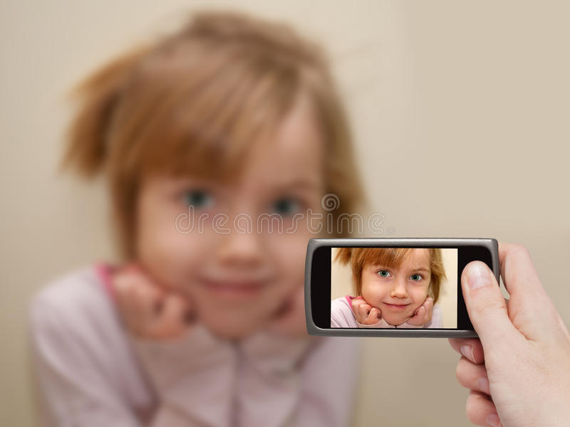 Man's hand making photo of a little girl with a mobile phone. royalty free stock images