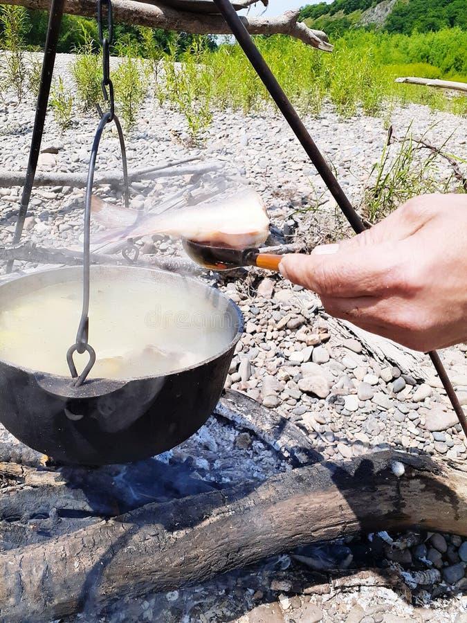 Man& x27; s-Hand mit einem hölzernen Löffel und einem Fisch auf ihm ein Eisentopf mit einer geschmackvollen Fischsuppe gemacht vo stockfoto