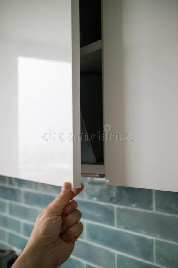 The man`s hand is opened by a modern hanging cabinet for a kitchen without door handles. The man`s hand opens a modern hanging cabinet for a kitchen without door royalty free stock photo