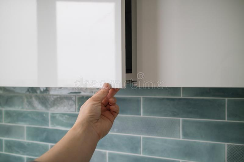 The man`s hand opens a modern hanging cabinet for a kitchen without door handles. Kitchen cabinet with doors without handles, the man`s hand shows how the doors stock photos