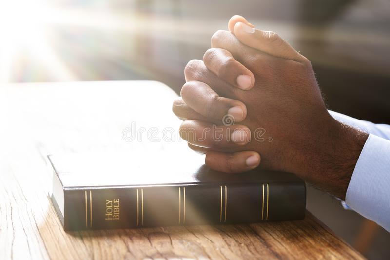 Man`s Hand Over Holy Bible Book royalty free stock images