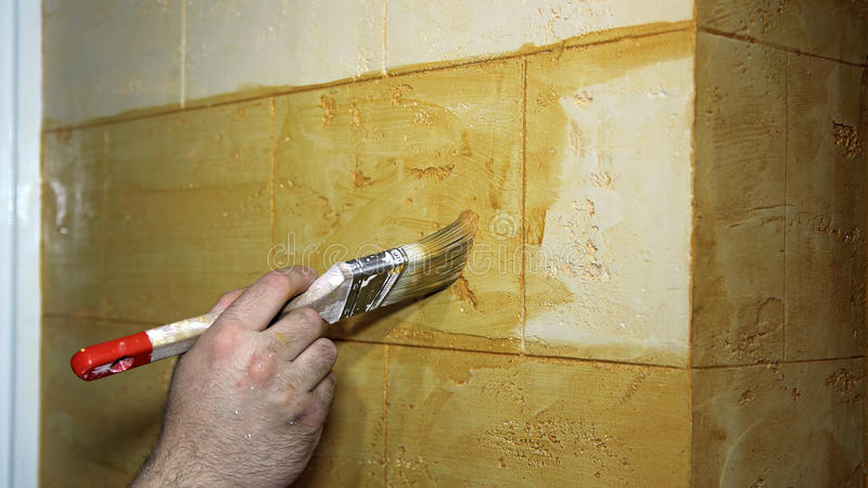 Man's Hand Painting A Wall With Paint Brush stock image