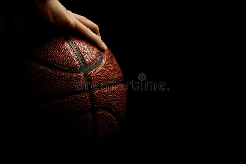 Man`s Hand Palming Basketball Isolated On Black Background, Copy Space Room stock image