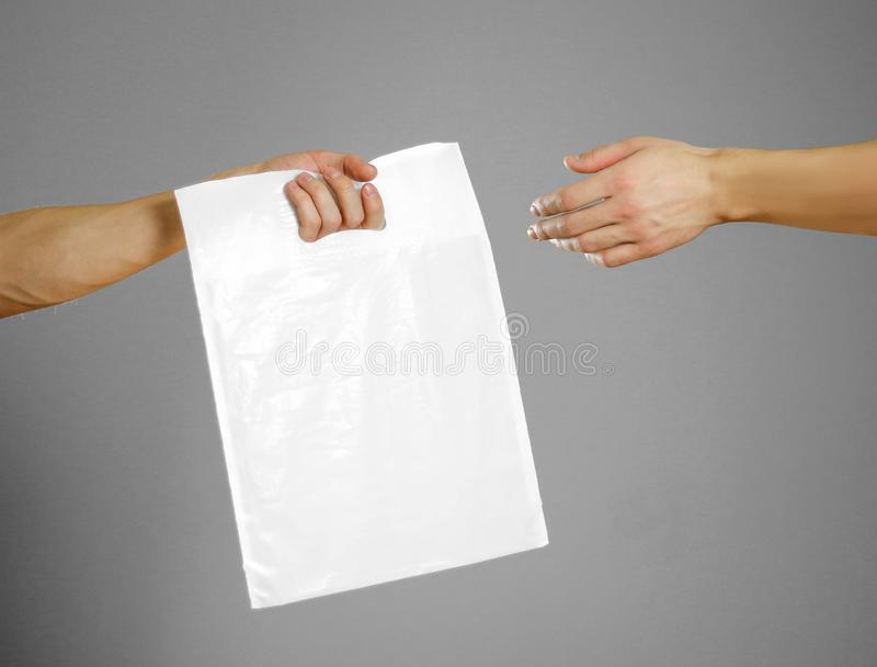 A man`s hand passes a white plastic bag. Close up. on grey background.  royalty free stock photo