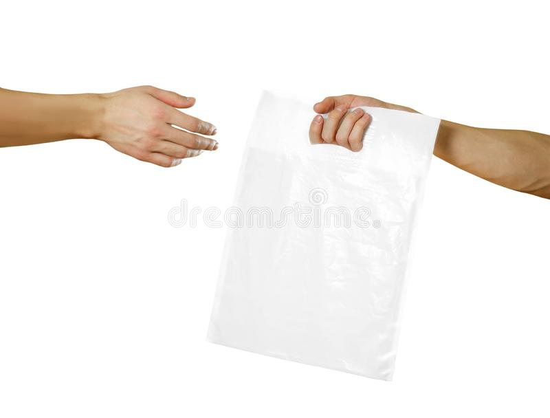 A man`s hand passes a white plastic bag. Close up. Isolated on white background.  stock photos