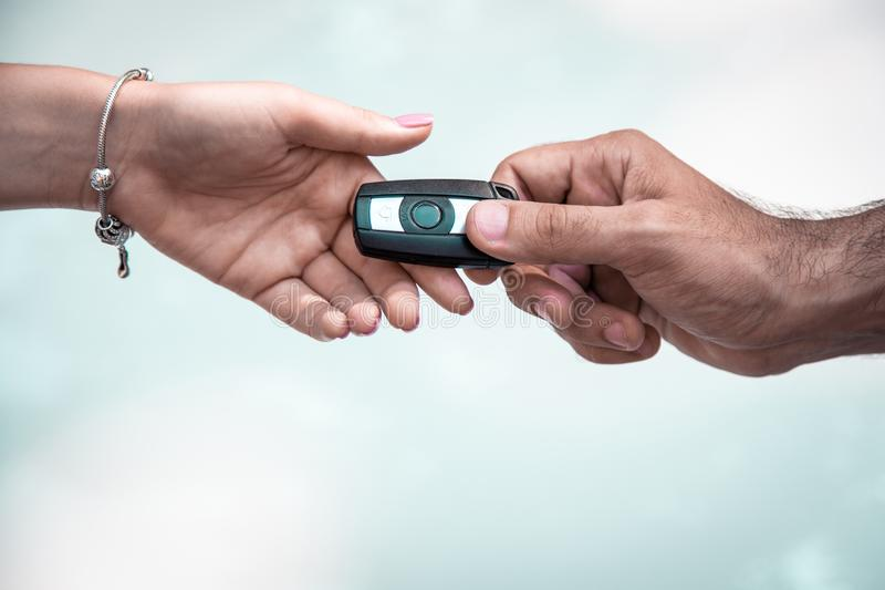 Man`s hand passing car keys to another hand against the sky. Good idea, man`s hand passing car keys to another hand against the sky royalty free stock photography