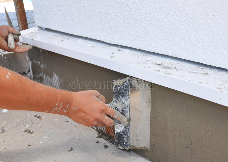 Man's hand plastering a wall insulation and house foundation with trowel. stock photos