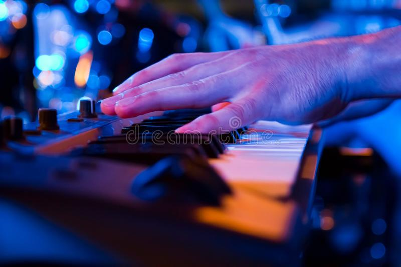 Man`s hand play the synthesizer at live concert in a pub, shallow dof, low key closeup photo. Man`s hand play keyboard of the synthesizer at live concert in a stock images