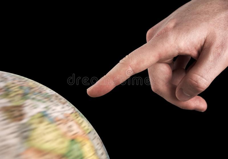 Man`s hand pointing to a rotating globe, isolated royalty free stock photo
