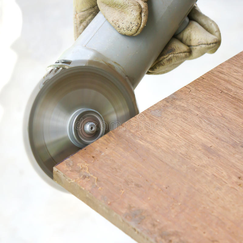 Man's hand polishing wooden board by saw machine. royalty free stock photo