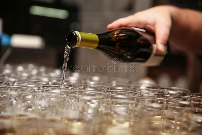 Man`s hand pours wine into glasses. The wine is poured from bottle to glass. the bartender fills glasses with sparkling wine royalty free stock photo