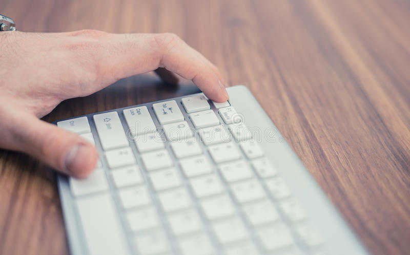 Man`s hand pressing escape button on wireless keyboard on wooden table stock photo