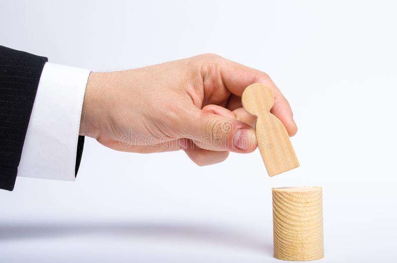 A man`s hand puts a person`s figure on top of his new post. A businessman appoints a person to a managerial position. stock photography