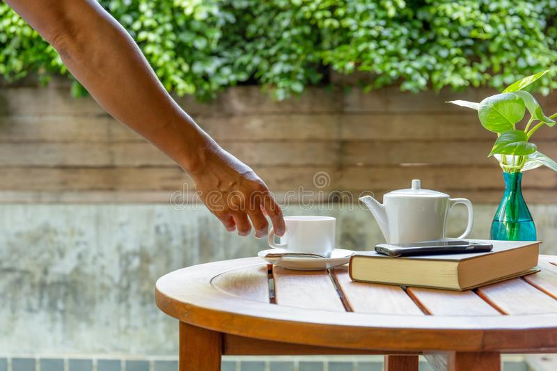 Man`s hand reaching for a coffee on wooden table. Man`s hand reaching for a coffee on wooden table royalty free stock photo