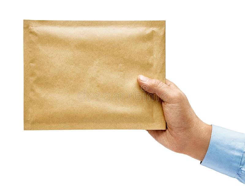 Man`s hand in shirt holds yellow envelope isolated on white background. Close up. High resolution product stock photo
