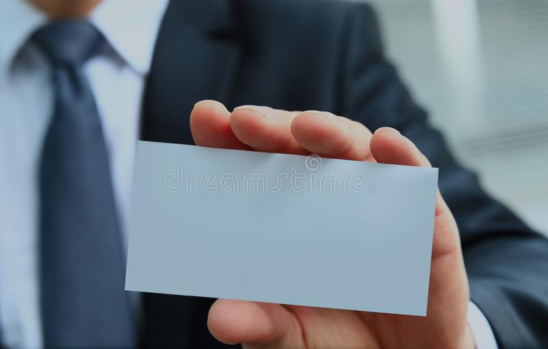 Man`s hand showing business card - closeup shot on grey background. stock images