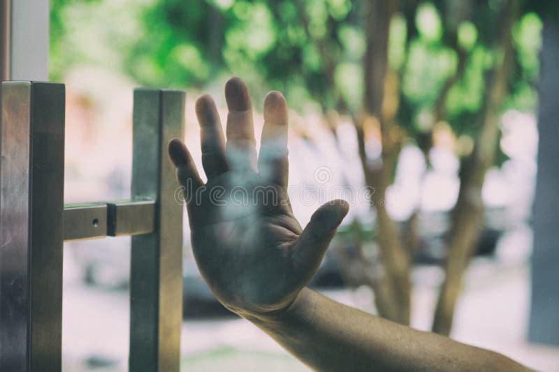 Man& x27; s-hand som skjuter, öppnande glass dörr arkivfoton