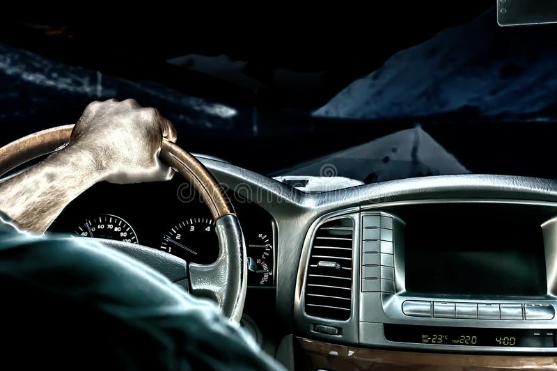 A man`s hand on the steering wheel of a car that moves along a night road among the mountains. Close-up of a man`s hand on the steering wheel of a car that moves stock photography
